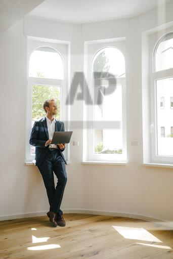 Estate agent waiting in newly refurbished home, holding laptop
