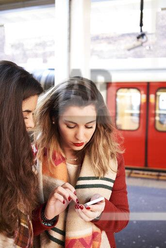 UK, London, two women using cell phone at underground station platform