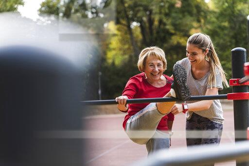 Grandmother and granddaughter training on bars in a park