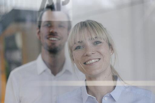 Successful businesswoman and businessman looking out of window, smiling