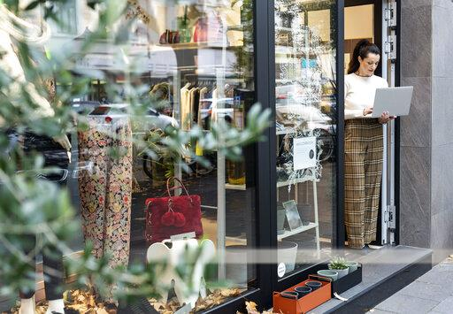 Shop owner standing in door of fashion store, using laptop
