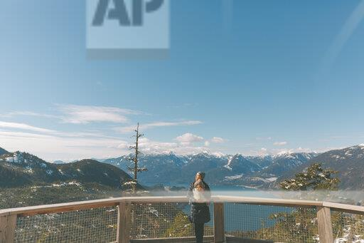 Mother holding her baby son on an observation deck, looking over Squamish, Canada
