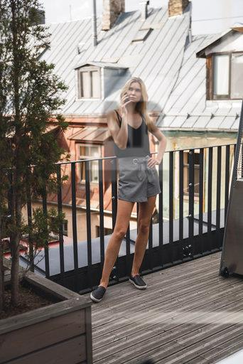 Serious blond woman on the phone standing on roof terrace