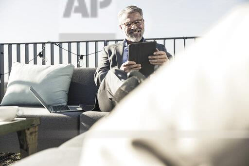 Smiling mature businessman using tablet on roof terrace
