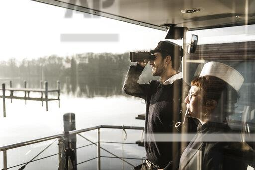 Colleagues working on a houseboat, watching surroundings with binoculars