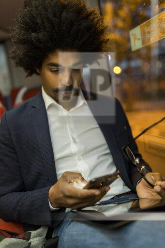 Spain, Barcelona, businessman in a tram at night using cell phone