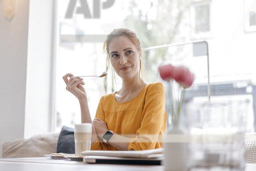Young woman working in coworking space, taking a break