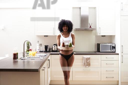 Smiling young woman carrying healthy breakfast tray in kitchen