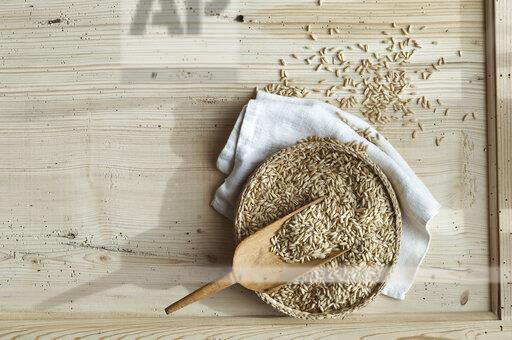 Organic oat, whole grains in bast bowl on wood, from above