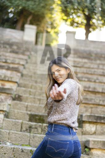 Portrait of a young woman on stairs reaching out her hand