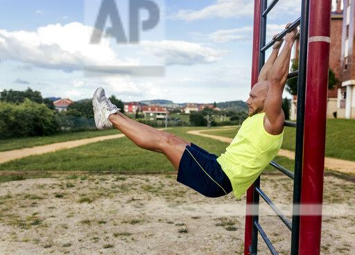 Muscular man exercising at a climbing frame outdoors