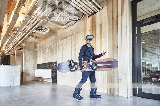 Mature businessman wearing VR glasses holding snowboard in modern office