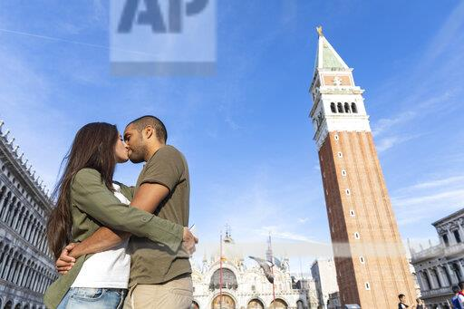 Italy, Venice, tourist couple kissing on St Mark's Square
