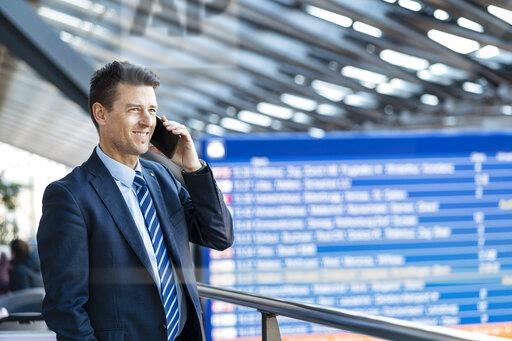 Smiling businessman on cell phone at the station