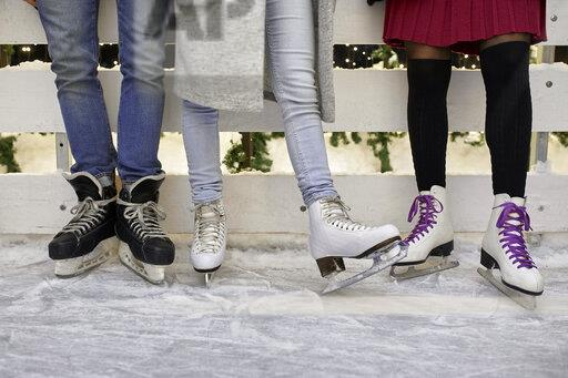 Legs of friends wearing ice skates standing at an ice rink