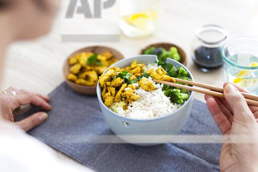 Curry chicken, broccoli and rice, woman with chopsticks