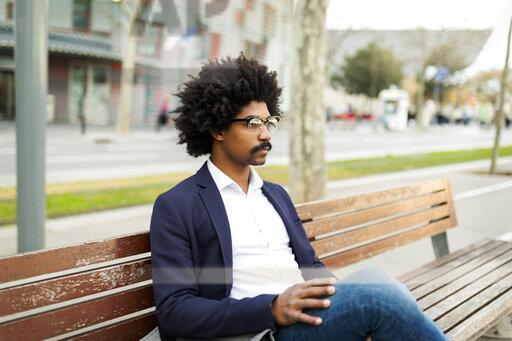 Spain, Barcelona, businessman in the city sitting on bench