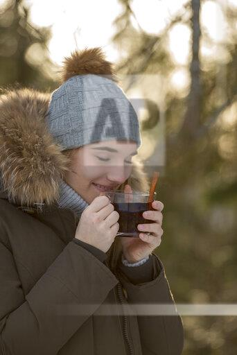 Portrait of young woman enjoying cup of tea in winter
