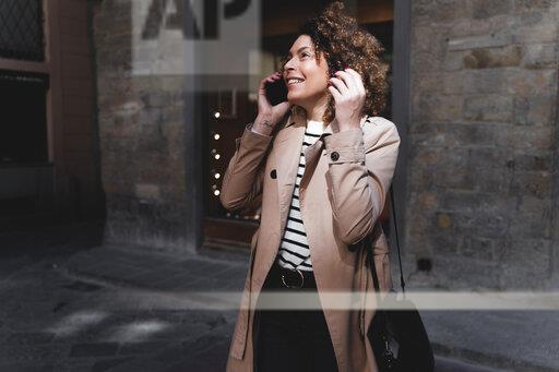 Smiling woman talking on cell phone in an alley
