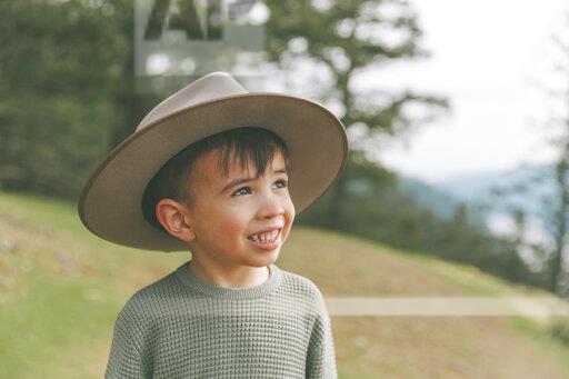 Portrait of a little boy, wearing his mother's hat