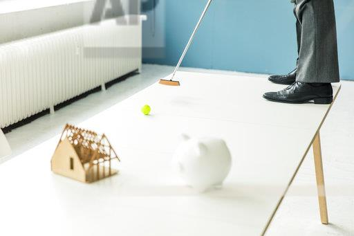 Close-up of businessman playing golf with piggy bank and house model on table in office