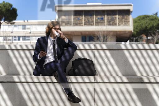 Italy, Florence, young businessman using smartphone with earbuds outdoor