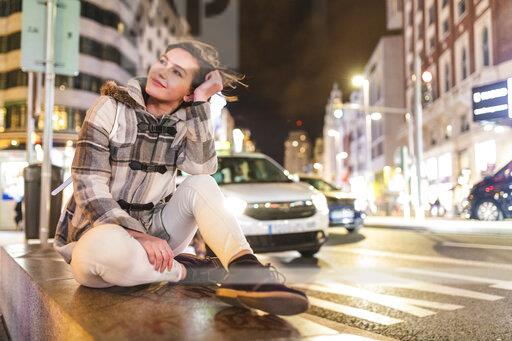 Spain, Madrid, young woman in the city at night next to Gran Via
