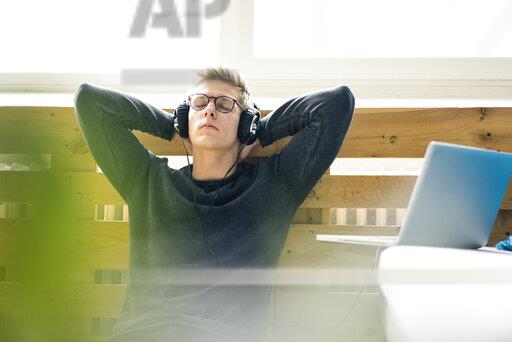 Relaxed young man sitting on the floor listening to music with headphones