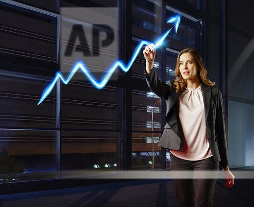 Businesswoman painting the stock market development with light