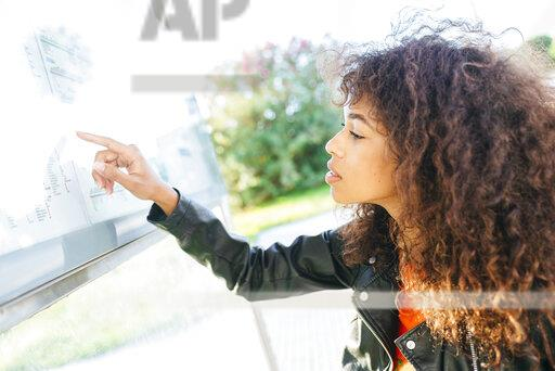 Young woman looking at schedule at bus stop