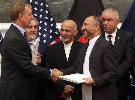 Afghanistan's national security adviser Mohmmad Hanif Atmar, second right, and NATO ambassador to Afghanistan Maurits Jochems, left, shake hands at the signing of the NATO-Afghanistan Status of Forces Agreement at the presidential palace, as Afghanistan's president Ashraf Ghani Ahmadzai, center, and chief executive Abdullah Abdullah, second left, attend in Kabul, Afghanistan, Tuesday, Sept. 30, 2014