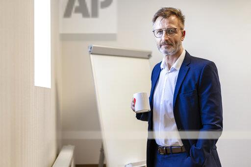 Portrait of businessman holding cup of coffee in office