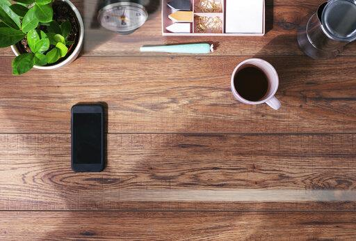 Wooden office desk with smartphone and coffee mug, top view