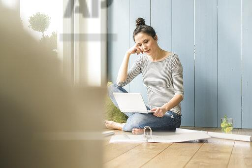 Woman sitting at the window at home working with laptop and file folder