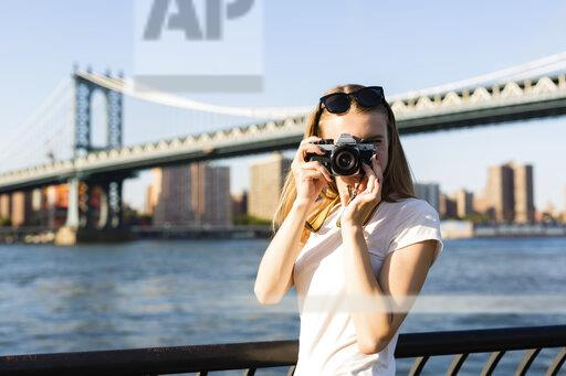 Young woman exploring New York City, taking pictures at Brooklyn Bridge