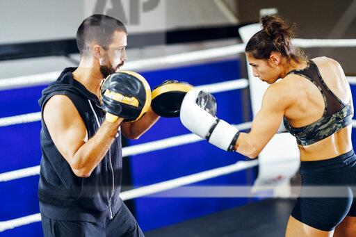 Female boxer sparring with her coach in gym