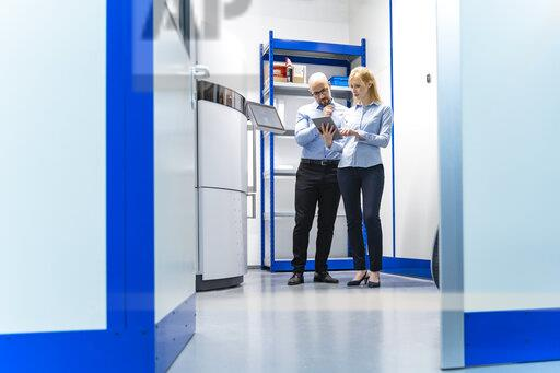 Businessman and businesswoman looking at tablet at 3d printer