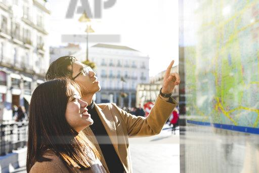 Spain, Madrid, young couple looking at the map and exploring the city