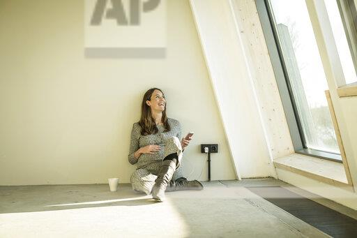 Pregnant woman drinking tea, sitting on floor of her new home