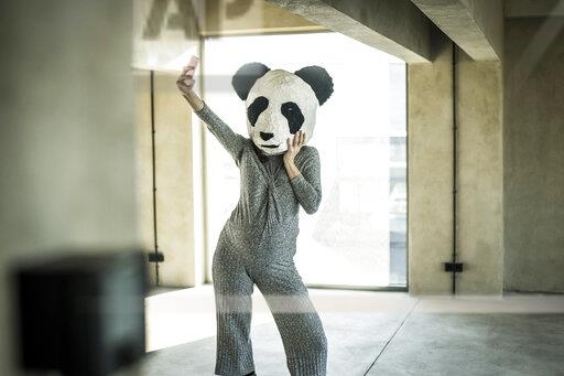 Woman with panda mask standing in office, taking selfie