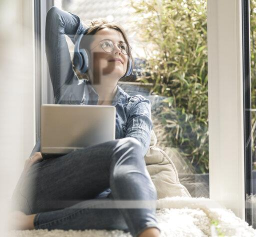Woman with headphones and laptop sitting at the window at home