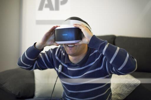 Laughing young man on couch at home using VR glasses