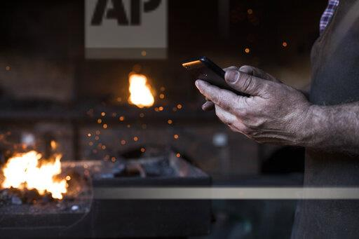 Close-up of blacksmith holding cell phone in his workshop