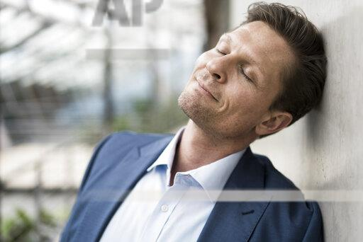 Businessman relaxing with eyes closed, leaning on wall