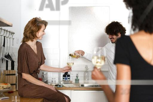 Friends having fun at a party, drinking wine in the kitchen
