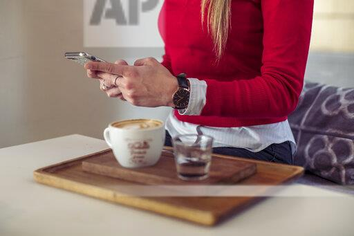 Woman using smartphone in a coffee shop, partial view
