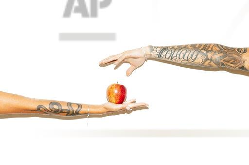 Woman's hand offering an apple to a man