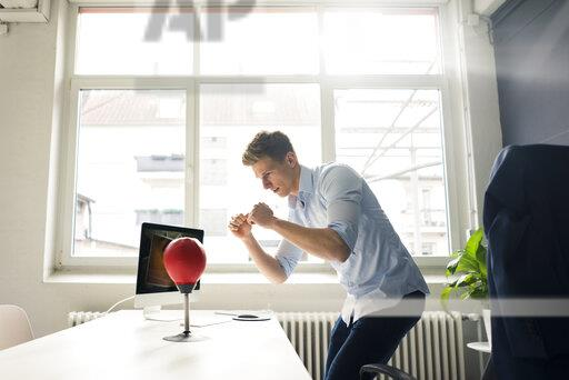 Young businessman at desk in office boxing with punching ball
