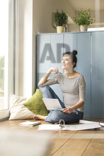 Smiling woman sitting at the window at home working with laptop and file folder