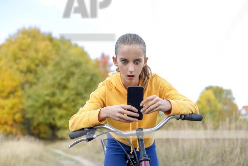 Portrait of girl leaning on bicycle starring at smartphone